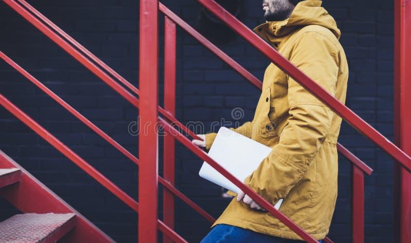有黄色背包、夹克和盖帽的行家在与计算机在手上,自由职业者的举行的膝上型计算机的红色减速火箭的梯子在春天起来 图库摄影