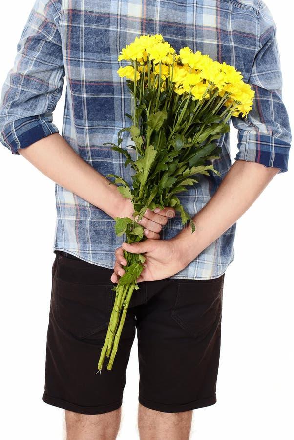 有黄色花花束的年轻人在他的后的  背景查出的白色 母亲节 华伦泰 背景概念框架沙子贝壳夏天 库存照片