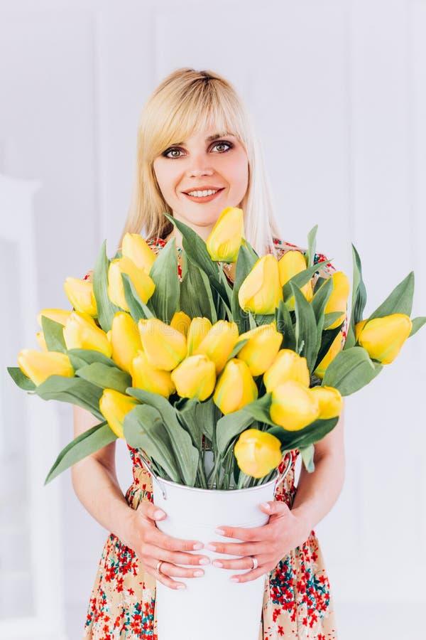 有黄色郁金香花束的一个少女金发碧眼的女人在她的手上见面春天 免版税库存照片
