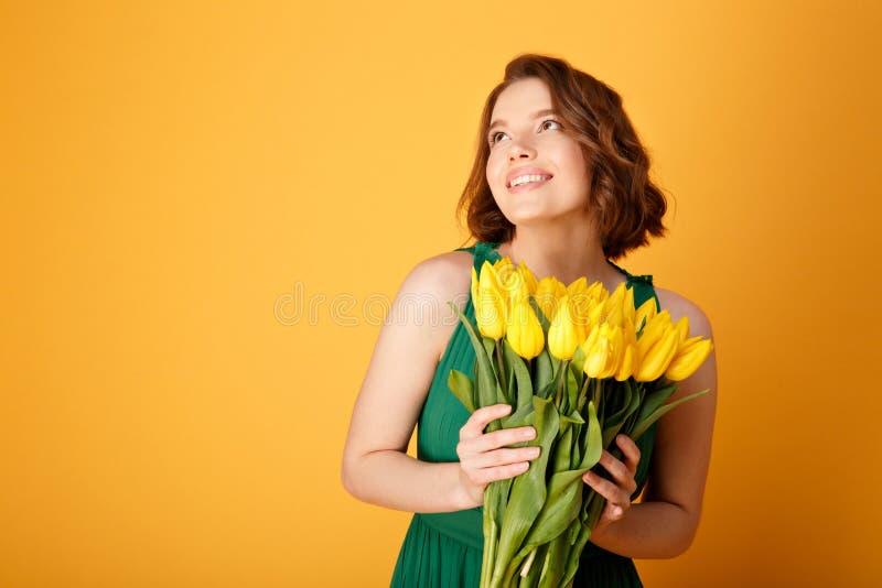 有黄色郁金香花束的画象pf梦想的妇女  免版税库存照片