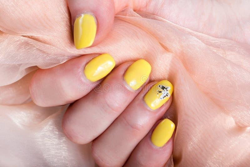 有黄色钉子的女性修剪拿着软的桃红色丝织物的擦亮剂 图库摄影