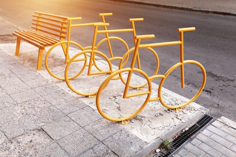 有黄色长凳的空的自行车停车处城市公园在背景 库存图片