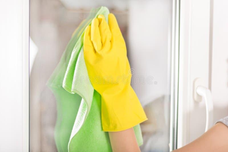 有黄色防护手套和绿色旧布清洁窗口的妇女手在家 免版税库存图片