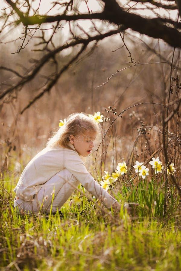 有黄色黄水仙的逗人喜爱的白肤金发的愉快的女孩在春天国家 免版税库存图片