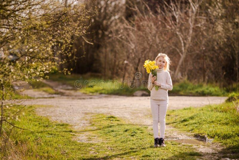 有黄色黄水仙的逗人喜爱的白肤金发的愉快的女孩在春天国家 库存图片