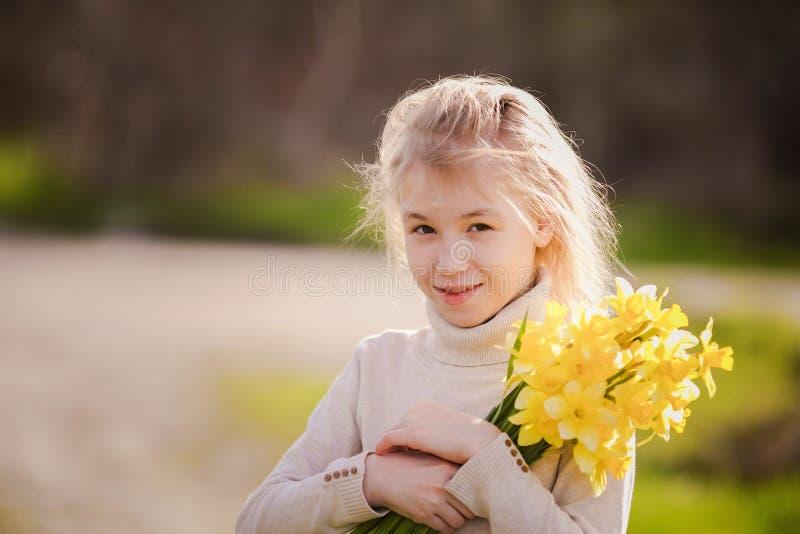 有黄色黄水仙的逗人喜爱的白肤金发的愉快的女孩在春天国家 库存照片