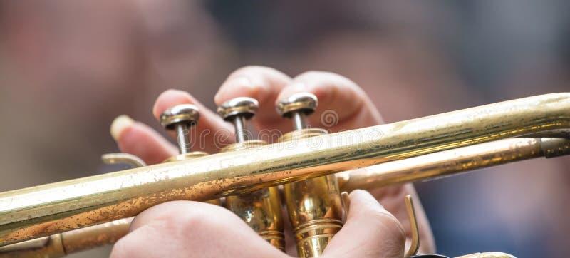 有黄铜喇叭的音乐家演奏古典音乐 关闭与细节的看法,被弄脏的背景,横幅 免版税库存照片