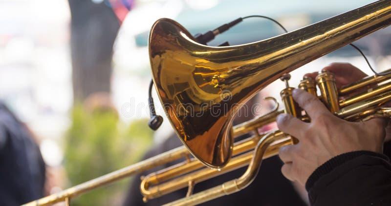 有黄铜喇叭的音乐家演奏古典音乐 关闭与细节的看法,被弄脏的背景 免版税库存图片