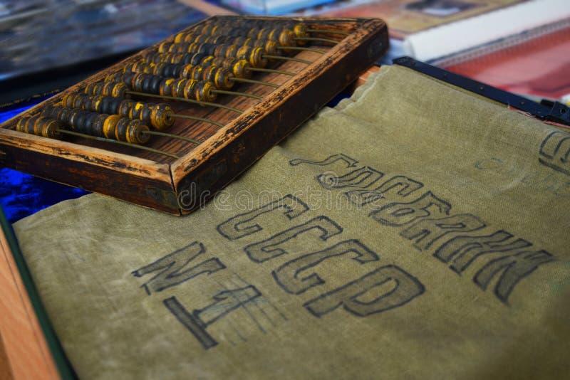 有黄麻袋的算盘硬币的 中国计算器和金钱袋子 与题字的袋子:苏联第1的国家银行 免版税库存图片