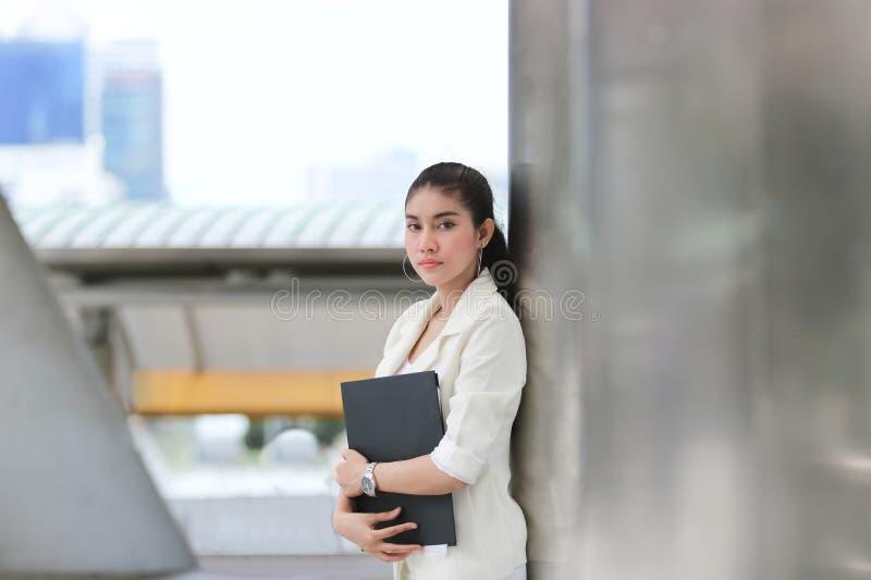 有黏合剂身分的可爱的年轻亚裔女商人在外部办公室 免版税库存照片