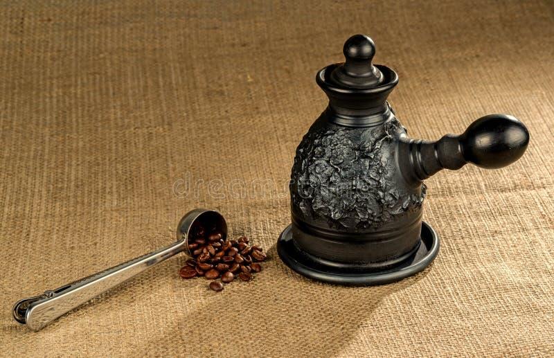 有黏土咖啡壶的钢量匙 免版税库存图片