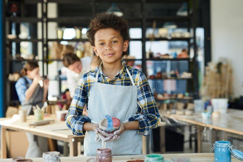 有黏土杯子的男孩 免版税库存照片