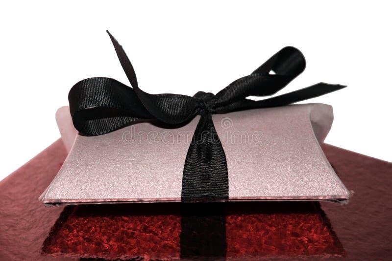 有黑丝带的被隔绝的礼物盒在红色闪光垫背景 免版税库存照片