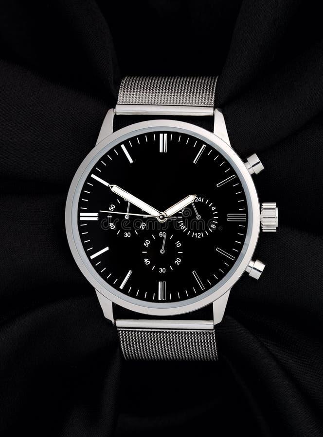 有黑体字的不锈钢手表在黑背景 免版税库存照片