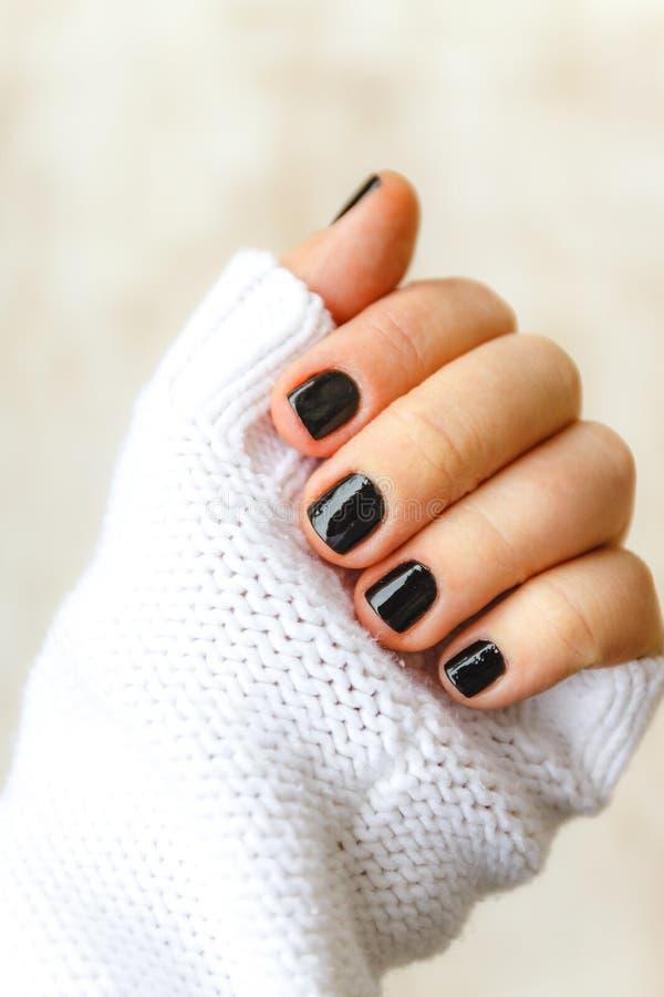 有黑修指甲的手在一件白色毛线衣的短的钉子在轻的背景 一个时髦和温暖的冬天的概念 免版税图库摄影