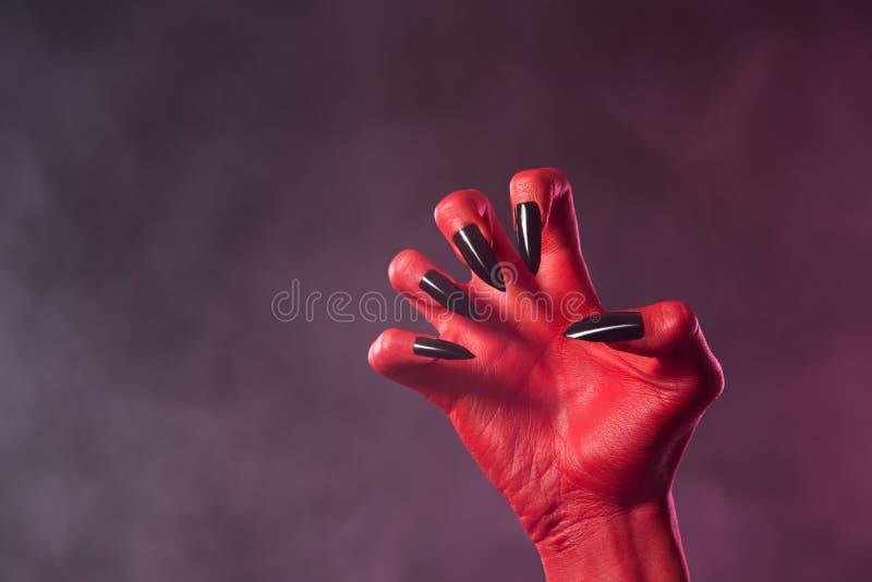 有黑光滑的钉子的红魔手 库存图片