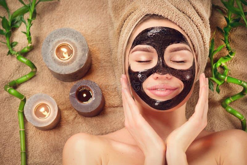 有黑净化黑面具的美女在她的面孔 秀丽有在温泉沙龙的黑面部脱层面具的模型女孩 免版税图库摄影