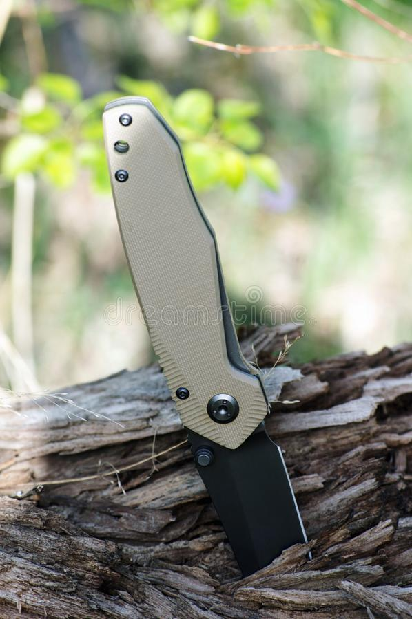 有黑刀片和把柄的折叠的旅游刀子由fibe制成 免版税图库摄影