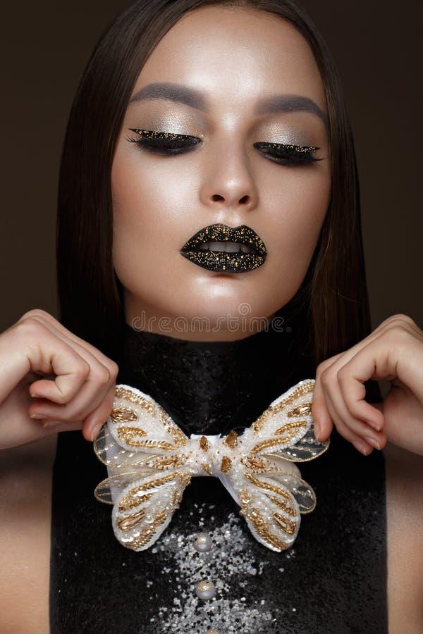 有黑创造性的艺术构成和金辅助部件的美丽的女孩 秀丽表面 库存照片