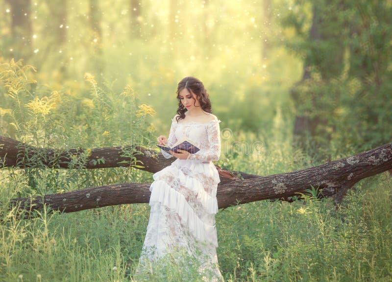 有黑发和光秃的肩膀的迷人的甜女孩在一件华美的葡萄酒白色礼服坐一棵下落的树并且读 图库摄影