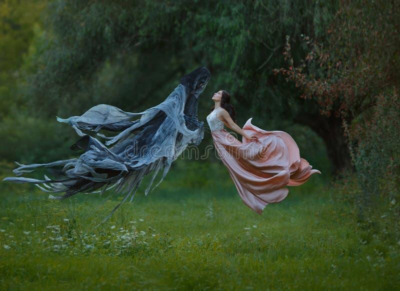 有黑发和整洁的理发的年轻苗条公主在天空中佩带了长的豪华振翼的飞行的礼服跳舞 库存照片
