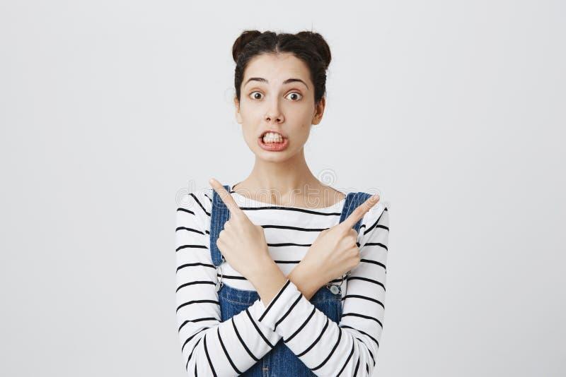 有黑发的俏丽的女孩在看照相机的hairbuns,害怕或震惊,握紧牙,指向她的食指 库存图片
