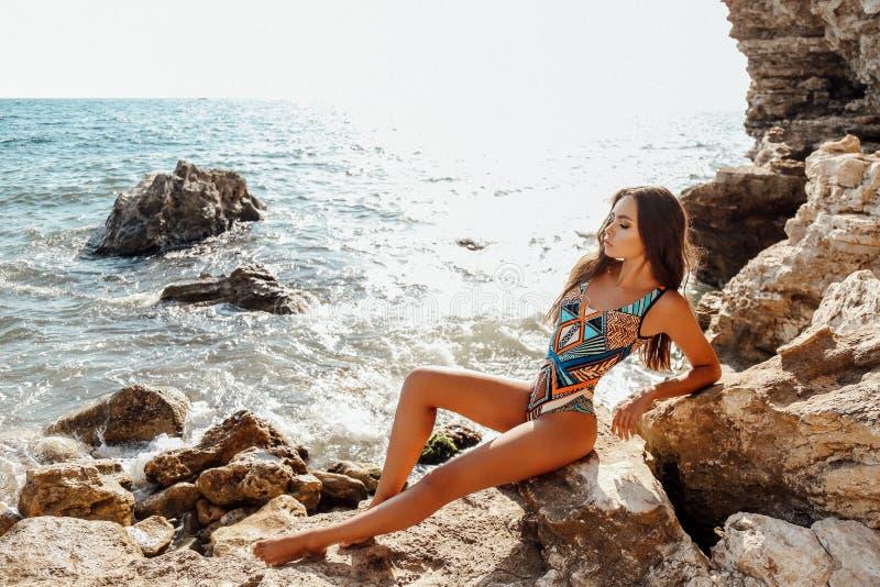 有黑发的女孩在摆在夏天海滩的典雅的游泳衣 免版税库存图片