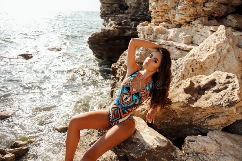 有黑发的女孩在摆在夏天海滩的典雅的游泳衣 库存照片
