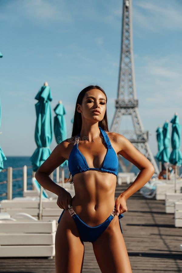 有黑发的女孩在摆在豪华海滩俱乐部的典雅的游泳衣 免版税库存照片