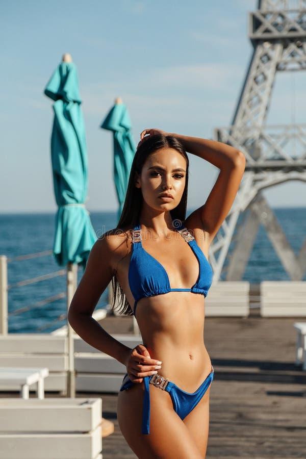 有黑发的女孩在摆在豪华海滩俱乐部的典雅的游泳衣 图库摄影