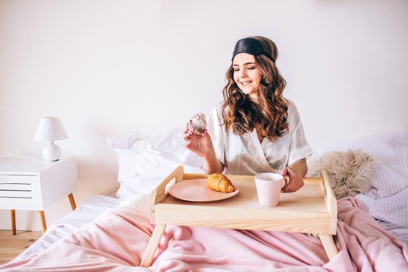 有黑发的年轻女人在手中坐床和举行蛋糕 早餐早晨 单独在卧室 美好的模型 免版税库存照片