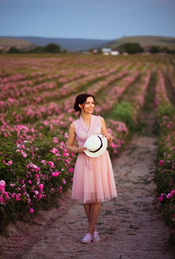 有黑发的美丽的在玫瑰的年轻女人和秸杆调遣 芳香、化妆用品和香水广告 库存图片