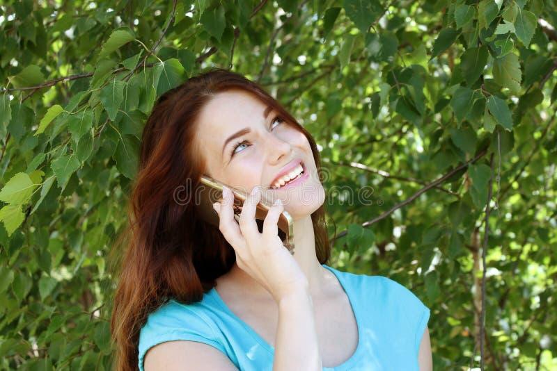 有黑发的美丽的女孩谈话在电话和笑以绿色树为背景的 免版税库存照片