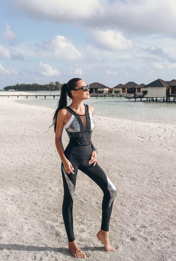 有黑发的美丽的妇女在放松在马尔代夫的体育衣服 库存图片