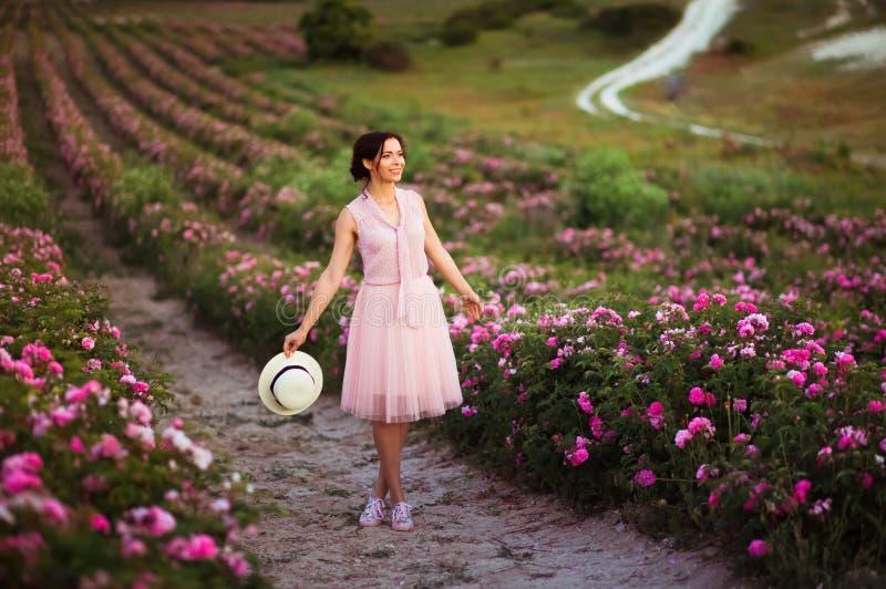 有黑发的美丽的年轻女人有在玫瑰的草帽的调遣 芳香、化妆用品和香水广告 免版税库存图片