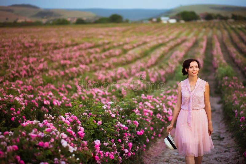 有黑发的美丽的年轻女人走在玫瑰的调遣 芳香、化妆用品和香水广告 库存图片