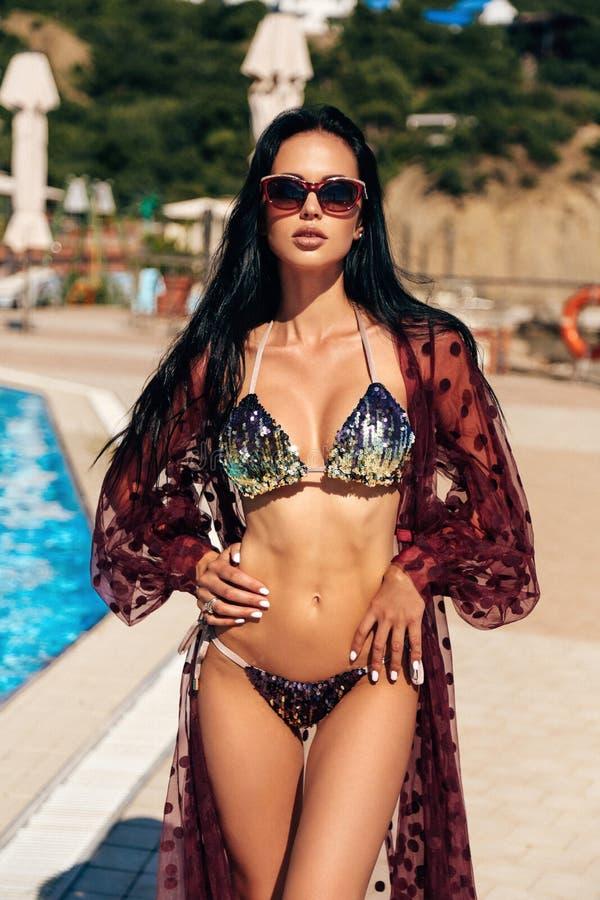有黑发的美丽的性感的妇女在摆在室外游泳场附近的典雅的游泳衣 免版税库存图片
