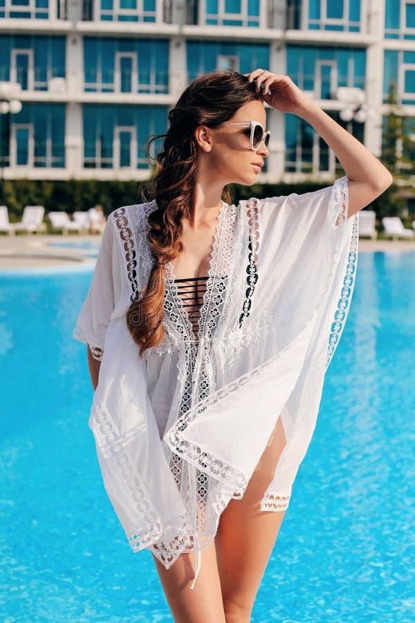 有黑发的美丽的性感的妇女在摆在露天游泳场附近的典雅的海滩衣裳 免版税图库摄影