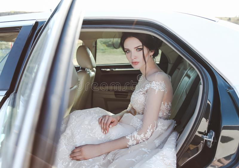 有黑发的美丽的新娘在典雅的婚礼礼服,摆在 免版税库存图片
