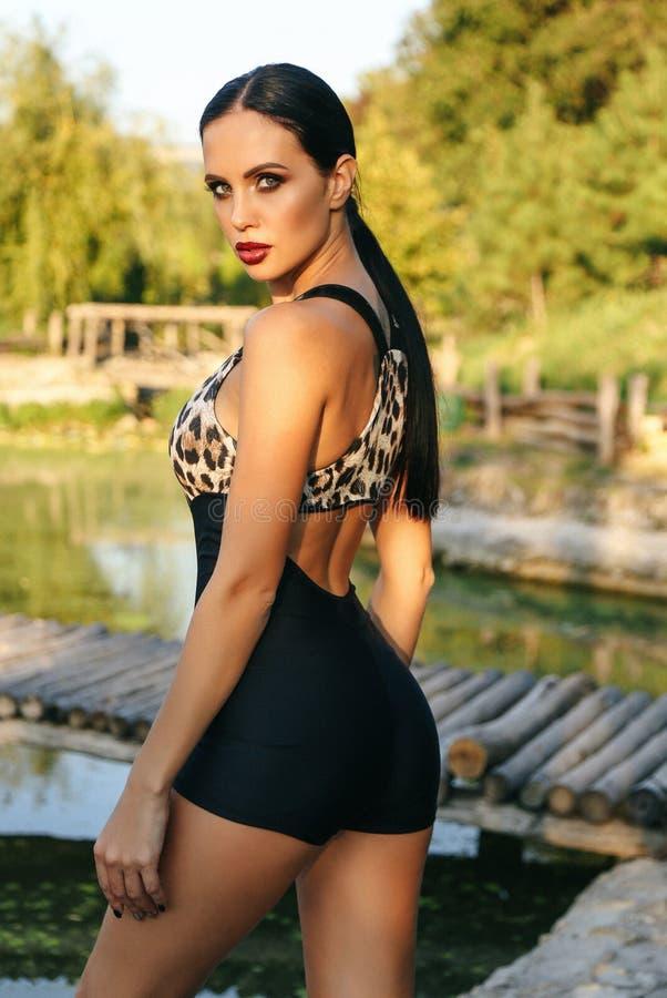 有黑发的美女在摆在湖附近的典雅的嬉戏衣服 免版税库存图片