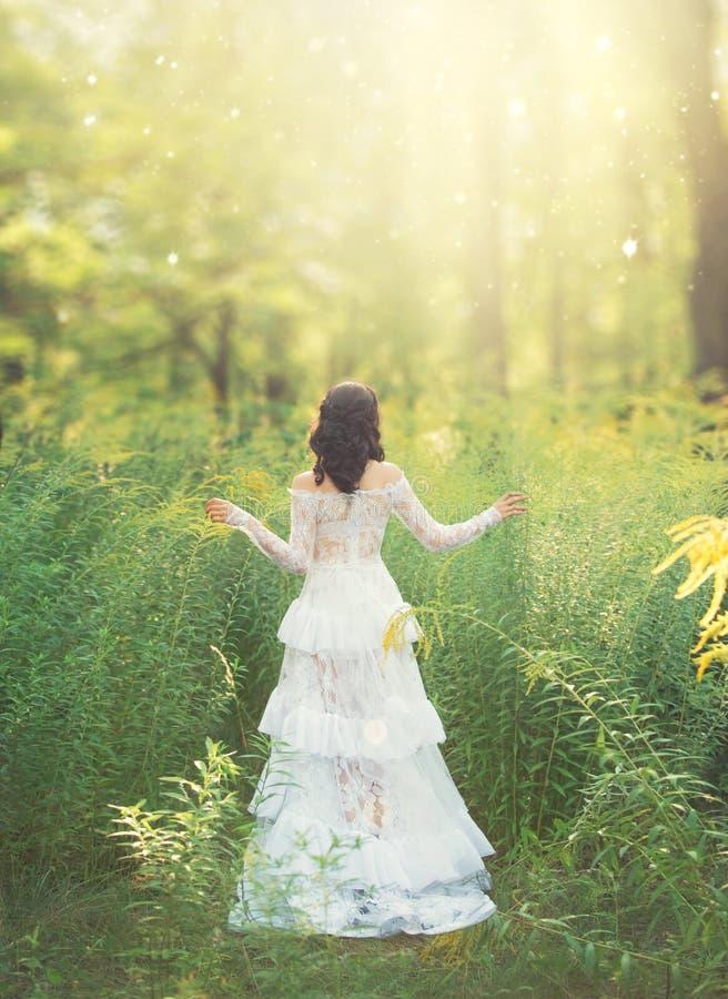 有黑发的迷人的甜女孩和在华美的白色礼服的光秃的肩膀立场有她的回到照相机在森林里 免版税库存照片