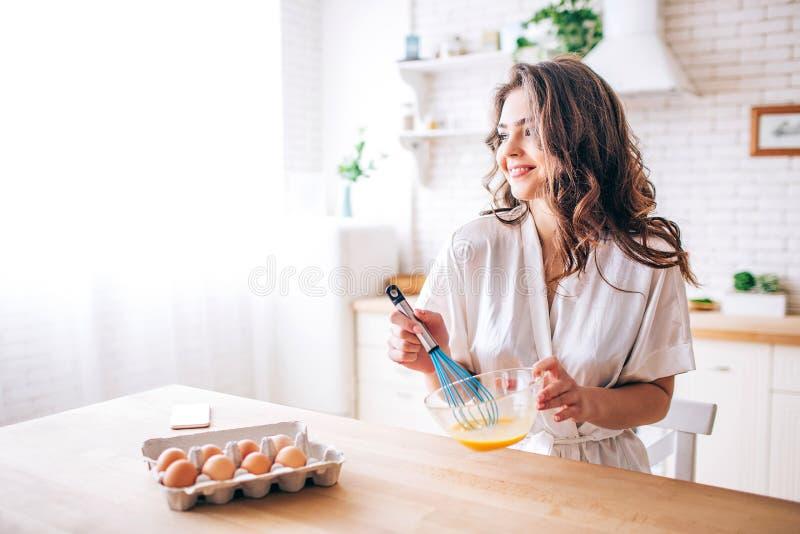 有黑发立场的年轻女人在厨房和烹调里 混和的鸡蛋 ?? 早晨白天 看平直和 免版税库存照片
