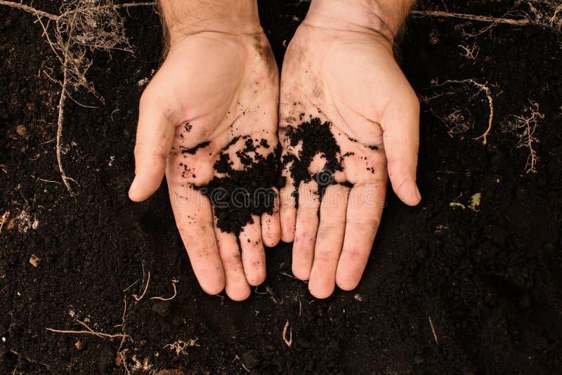 有黑土壤的男性手 图库摄影