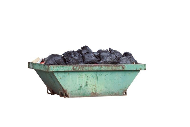 有黑垃圾袋的绿色生锈的容器 免版税库存照片