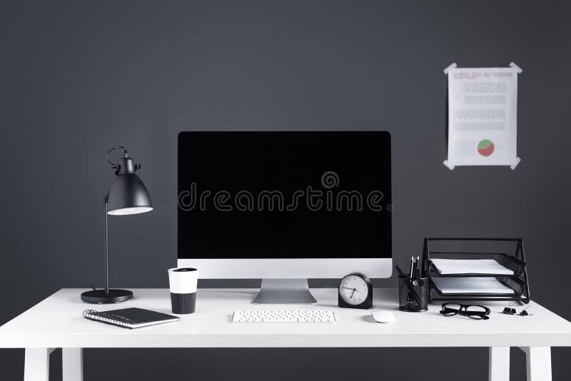 有黑屏、企业图、时钟和办公用品的台式计算机 免版税库存图片