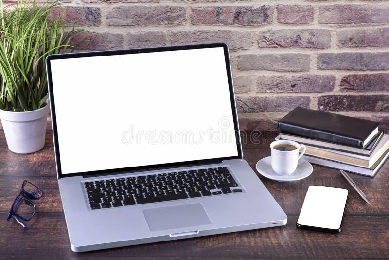 有黑屏和咖啡的膝上型计算机笔记本和智能手机在木桌上 免版税库存图片
