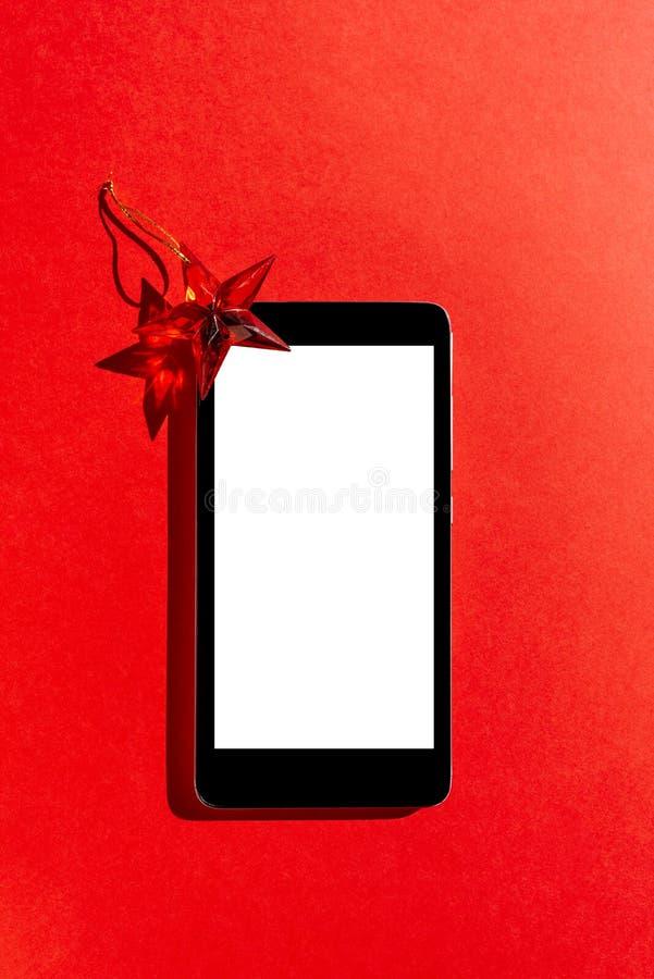 有黑屏和装饰星的手机在红色背景 顶视图 库存图片
