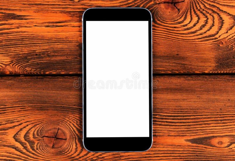 有黑屏嘲笑的手机在黄色木桌背景 在木表上的智能手机 智能手机白色屏幕 免版税库存照片