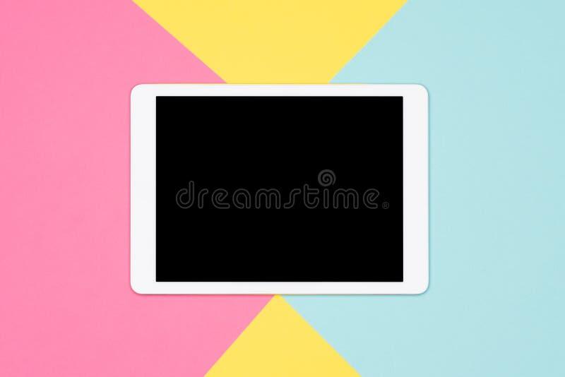 有黑屏嘲笑的数字式片剂在柔和的淡色彩的平的位置上色了背景 在五颜六色的背景的片剂 免版税库存照片