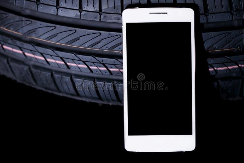 有黑屏幕的一白色智能手机有后边轮胎的和隔绝在黑色 库存照片